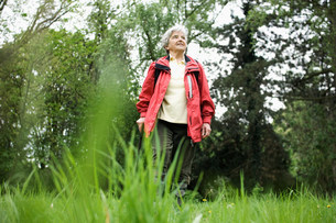 Older woman walking in parkの写真素材 [FYI03585473]