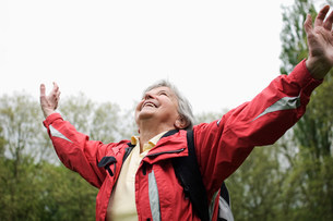 Older woman cheering in parkの写真素材 [FYI03585474]