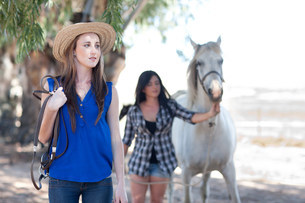 Two young women leading horseの写真素材 [FYI03585745]