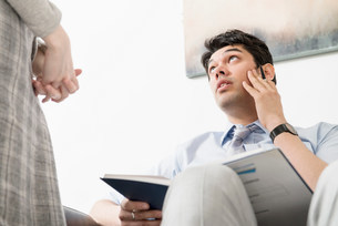 Man looking up towards female colleagueの写真素材 [FYI03585973]