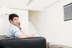 Man sitting on sofa in foyer looking at cameraの写真素材 [FYI03585976]