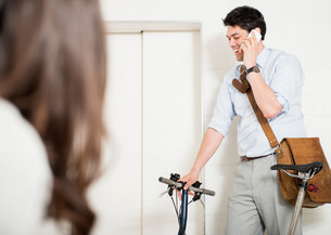 Man on cell phone by elevator with bikeの写真素材 [FYI03585982]