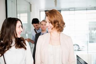 Female colleagues in office corridor with men in backgroundの写真素材 [FYI03585988]