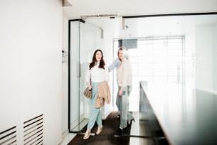 Female colleagues walking through office doorwayの写真素材 [FYI03585991]
