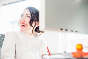 Female office worker looking away, smilingの写真素材 [FYI03585999]