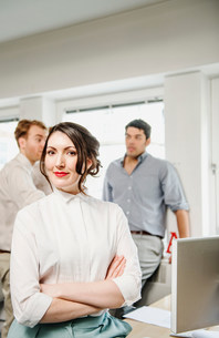 Portrait of female office worker, male colleagues in backgroundの写真素材 [FYI03586008]