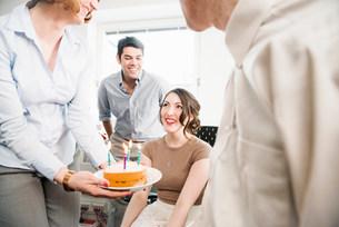 Female office worker receiving birthday cakeの写真素材 [FYI03586012]