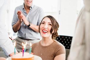 Female office worker receiving birthday cakeの写真素材 [FYI03586013]