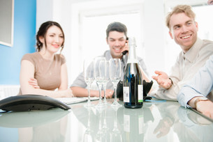 Colleagues with champagne bottle and glasses ready on tableの写真素材 [FYI03586020]