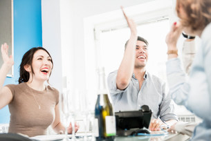 Colleagues giving high fives in office, champagne on tableの写真素材 [FYI03586022]