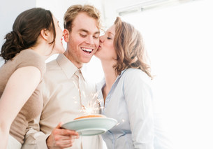 Female colleagues kissing man on cheek with birthday cakeの写真素材 [FYI03586033]