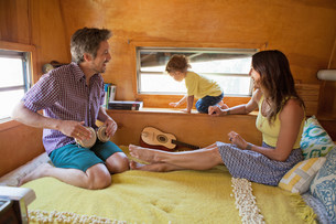 Parents and son on bed in trailer homeの写真素材 [FYI03586221]