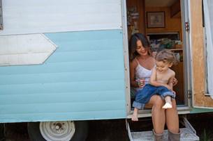 Mother and son sitting in doorway of motor homeの写真素材 [FYI03586233]