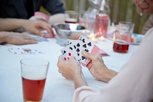Friends playing card game at garden partyの写真素材 [FYI03586326]