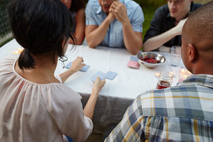 Friends playing card game at garden partyの写真素材 [FYI03586345]