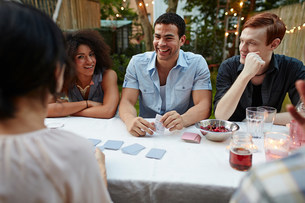 Friends playing card game at garden partyの写真素材 [FYI03586348]