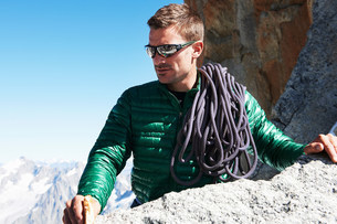 Portrait of mountaineer with climbing rope over shoulderの写真素材 [FYI03586527]