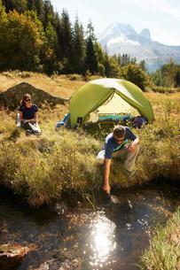 Couple camping by stream, Chamonix, Haute Savoie, Franceの写真素材 [FYI03586534]