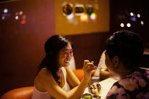 Young couple sharing dessert in cafeの写真素材 [FYI03586597]
