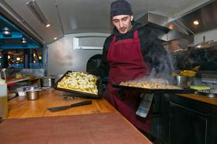 Chef preparing pizzas in food stall van at nightの写真素材 [FYI03586786]