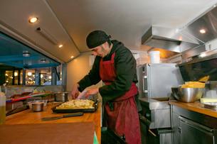 Chef preparing pizza in food stall van at nightの写真素材 [FYI03586788]