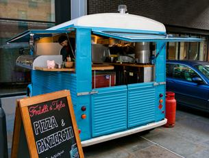Chef preparing pizza in vintage van parked outside office buildingsの写真素材 [FYI03586789]