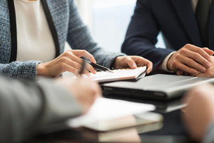 Cropped shot of businesswoman and man making notes in office meetingの写真素材 [FYI03586799]