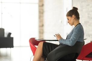 Businesswoman sitting in office looking at smartphoneの写真素材 [FYI03586810]