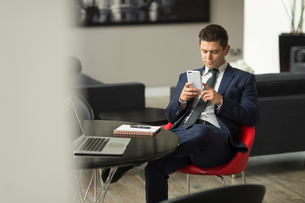 Businessman sitting in office looking at smartphoneの写真素材 [FYI03586817]