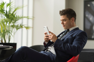 Businessman sitting in office looking at smartphoneの写真素材 [FYI03586819]