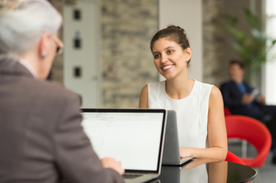 Young businesswoman and female colleague talking over office deskの写真素材 [FYI03586844]