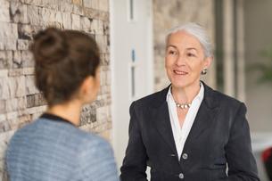 Over shoulder view of mature businesswomen talking in officeの写真素材 [FYI03586850]