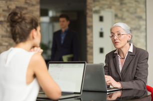 Mature businesswoman and female colleague having discussion over office deskの写真素材 [FYI03586851]