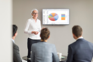 Over shoulder view of mature businesswoman giving office presentationの写真素材 [FYI03586852]