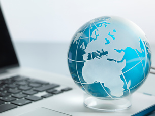Globe and laptop on deskの写真素材 [FYI03587028]