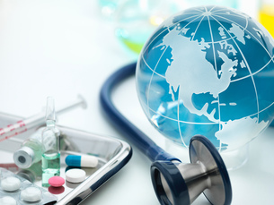 Globe showing the Americas with acoustic stethoscope and surgical tray with medicinesの写真素材 [FYI03587029]