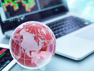 Globe with digital tablet and laptop showing international business tradeの写真素材 [FYI03587034]