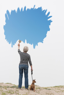 Senior woman with dog on lead painting blue sky in airの写真素材 [FYI03587190]
