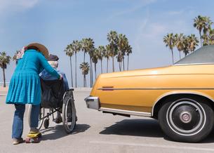 Senior woman pushing husband in wheelchair by vintage car at Venice Beach, California, USAの写真素材 [FYI03587341]