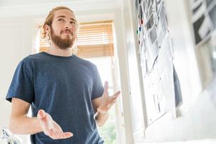Young male designer explaining mood board idea in creative studioの写真素材 [FYI03587348]