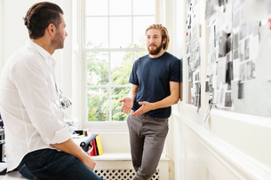 Young male designer explaining mood board idea to colleague in creative studioの写真素材 [FYI03587350]