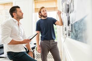 Young male designer explaining mood board idea to colleague in creative studioの写真素材 [FYI03587352]