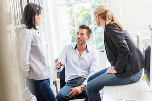Male designer explaining idea to female colleagues in creative studio meetingの写真素材 [FYI03587405]