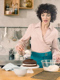 Woman decorating chocolate cake with dairy creamの写真素材 [FYI03587418]