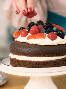Woman decorating chocolate cake with dairy cream and fresh summer fruitsの写真素材 [FYI03587419]