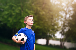 Boy holding soccer ball looking awayの写真素材 [FYI03587425]