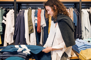 Shopper making decision in clothes shopの写真素材 [FYI03587464]