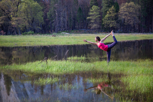 Woman practicing yoga tree pose by lake in Yosemite National Park, California, USAの写真素材 [FYI03587521]