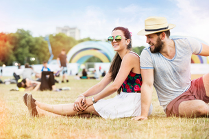 Couple sitting on grass together at festivalの写真素材 [FYI03587525]
