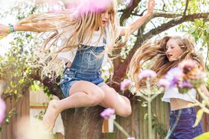 Girls in garden jumping in airの写真素材 [FYI03587554]